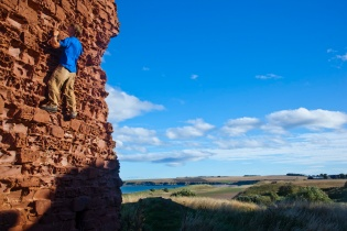 Climbing the castle at Lunan bay